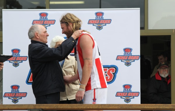 Josh Jewell accepts the Yeomans Medal as BOG in 2014 Division 2 Reserve Grand Final. He has since established himself as number 1 defender in the Bloods senior team.