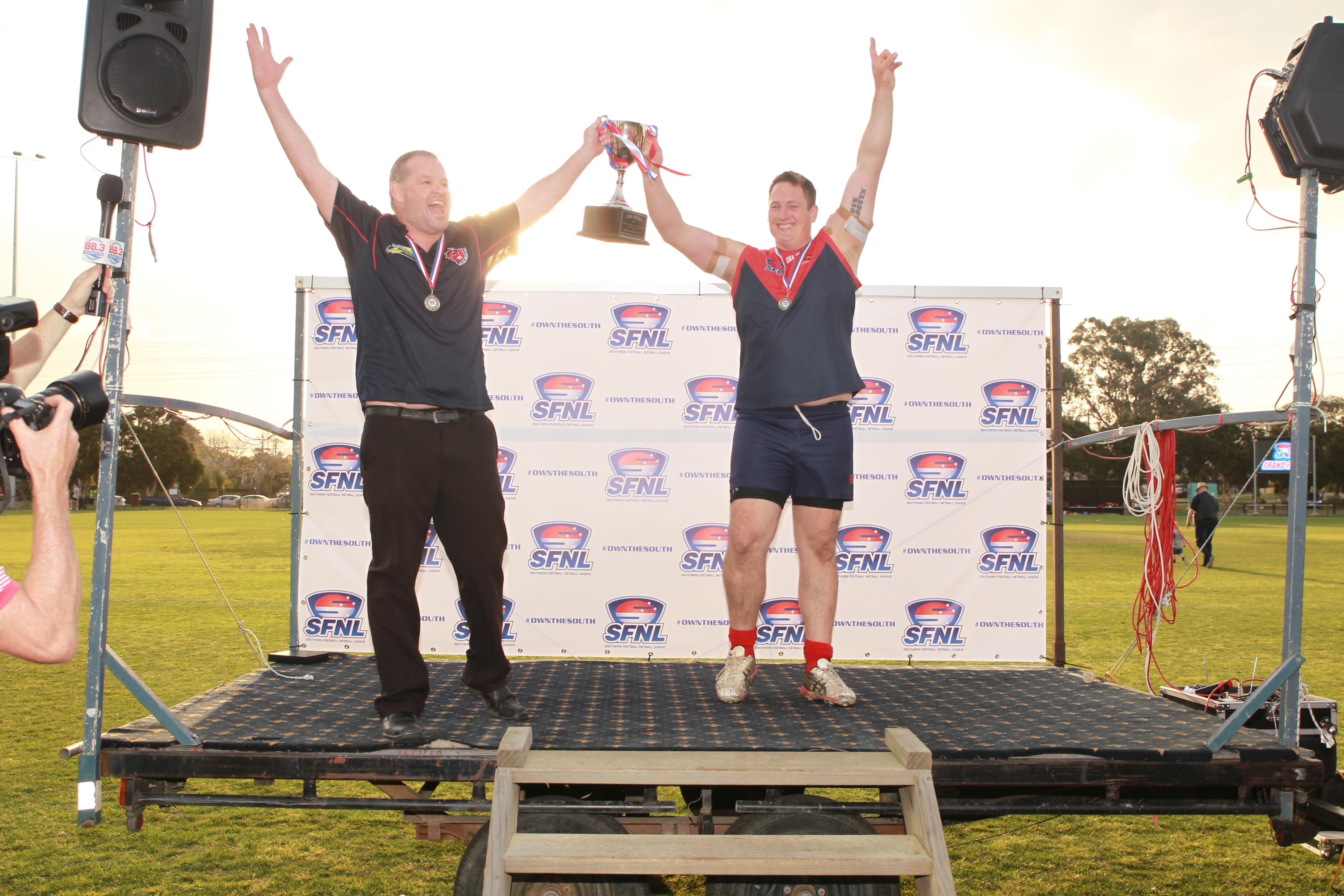 Coach Brad Canavan and Captain Phil Smith hoist the 2017 premiership cup.